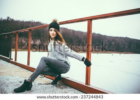 Young pretty girl on the bridge with forest and lake on background - stock photo
