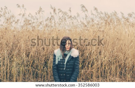 Young pretty girl on the lake in autumn day - stock photo