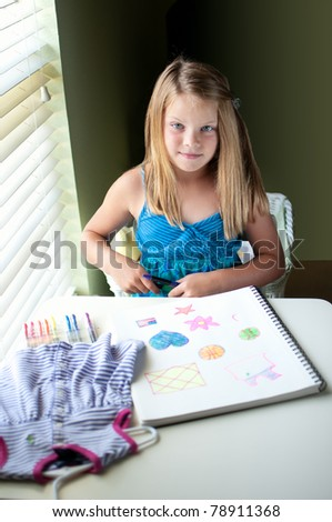 Young pretty girl sitting by window in room drawing colorful images - stock photo