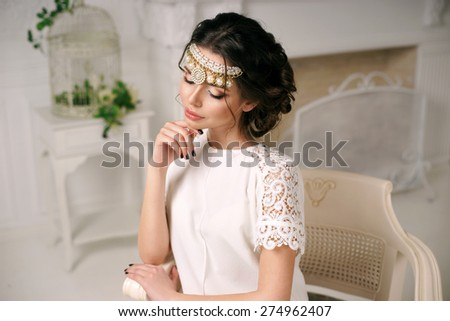 Young pretty girl sitting in luxury armchair and posing. Portrait in lovely soft tender light and colors - stock photo
