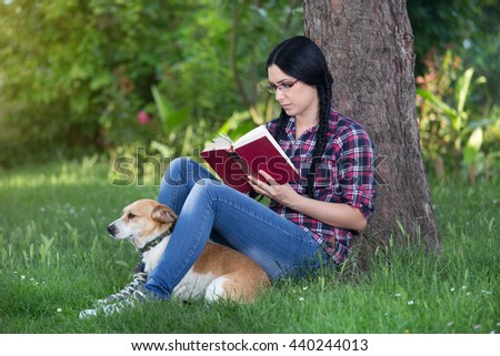 Young pretty girl sitting on grass leaning on tree in park and reading book with cute dog beside her - stock photo