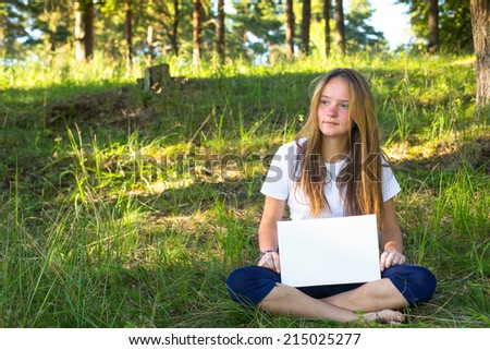 Young pretty girl sitting on the nature of holding a white banner. - stock photo