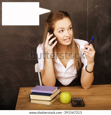 young pretty girl student in classroom at blackboard - stock photo