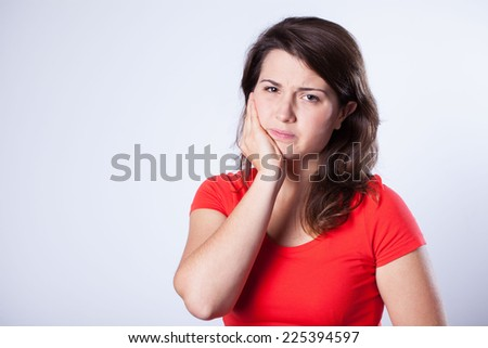 Young pretty girl with horrible pain in tooth - stock photo