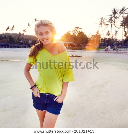 Young pretty happy blonde smiling and looking on camera, posing at californian beach at sunset. - stock photo