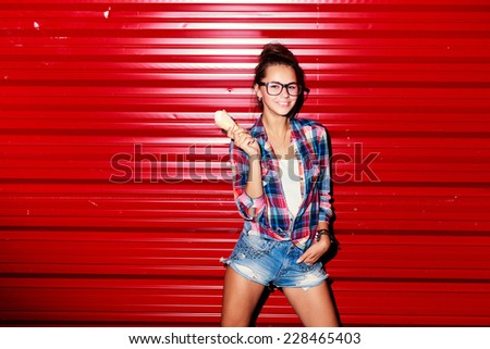 Young pretty happy sport style tanned girl posing in summer night on red wall background and have fun  - stock photo