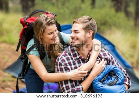 Young pretty hiker couple holding a sleeping bag and backpack in the nature - stock photo
