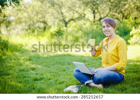 Young pretty hipster girl with laptop in a park with coffee cup - stock photo