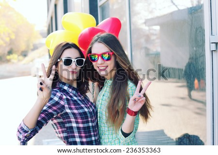 Young pretty hipster girls friends having fun outdoor in summer on the street. Vintage lifestyle trendy portrait. Photo toned style Instagram filters. - stock photo