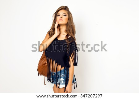 Young pretty hipster woman in black trendy t-short and bikini posing on the floor against white wall.Have perfect long wavy hairstyle wearing casual leather brown bag and indie pop outfit,wavy hair - stock photo