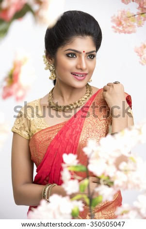 Young pretty Indian woman in traditional saree in flower garden in studio shoot. - stock photo
