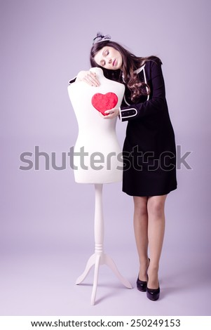 Young pretty lady in classic black dress giving heart to mannequin on studio background - stock photo