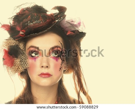 Young pretty lady with creative make-up and in exotic hat. - stock photo