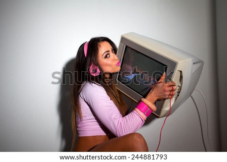 Young Pretty Latino Woman sitting in a hotel room lifting a vintage television set above her head - stock photo
