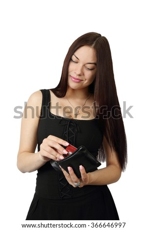 Young pretty long haired brunette woman in black dress takes credit card from purse isolated on white background - stock photo