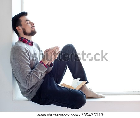 Young pretty man sitting on the window with cup of tea and book  isolated on white background - stock photo