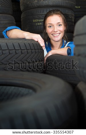Young, pretty, mechanic, surrounded by stacks of car tyres with varous treads, sizes and compounds, smiling - stock photo