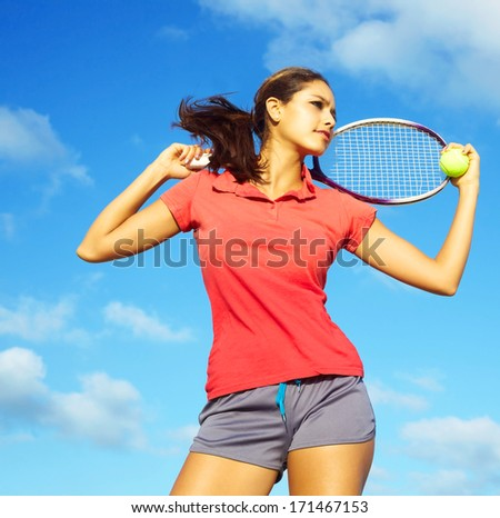 Young pretty mixed race female athlete playing tennis in the court with nice blue sky background. Horizontal Shot, color image, copy space. - stock photo