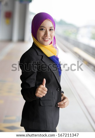 Young Pretty Muslim girl at the Train station - stock photo