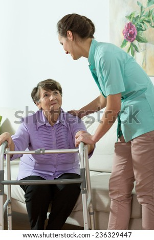 Young pretty nurse helping older lady with walker to stand up - stock photo