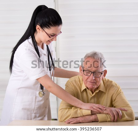 Young pretty nurse holding her hands on the shoulder and hands of old man and smiling. Concept of senior people care - stock photo