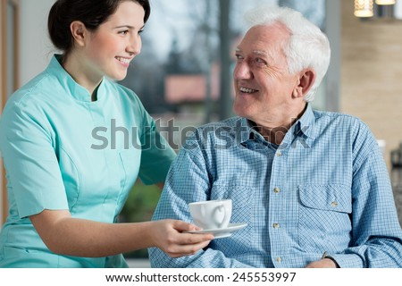 Young pretty nurse serving the cup of coffee to elderly smiling man - stock photo
