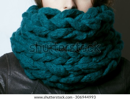young pretty real woman in blue sweater and scarf all over her face smiling - stock photo