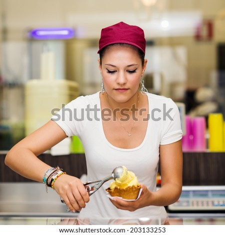 Young pretty saleswoman portrait inside ice cream shop. - stock photo