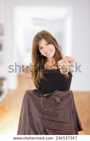 Young pretty smiling female hairdresser with comb and scissors waiting impatiently for customer at home or salon and calling you or someone. Concept of great work in profession and enjoying job - stock photo