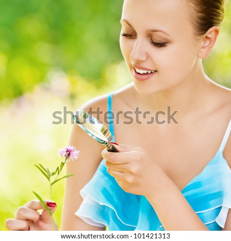 Young pretty smiling woman examining with a magnifying glass flower at summer green park - stock photo