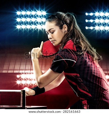 Young pretty sporty girl playing table tennis on black background with lights - stock photo