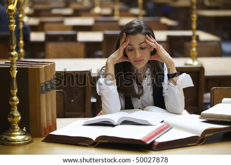 Young pretty student sitting at desk in old university library studying books. - stock photo