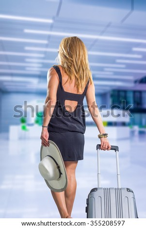 Young pretty stylish woman with luggage at the international airport - stock photo