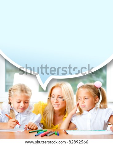Young pretty teacher helping to her students to make exercise indoors at classroom. Copyspace. Vertical Shot. Blank balloon with copyspace for your text and logo. - stock photo