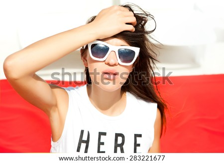 Young pretty teen girl with wearing stylish hipster outfit,and  fashionable shirt.Party concept.posing on the beach resort background, bright summer fashion portrait.Here and now sign shirt. - stock photo