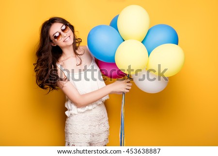 Young pretty teenage girl posing over yellow background, holding colorful balloons, wearing fashionable sunglasses. Summer style. Studio shot. - stock photo