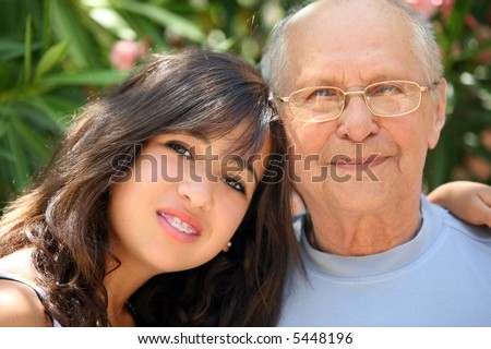 Young pretty woman and her grandfather - stock photo