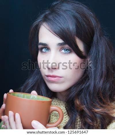 young pretty woman drinking tea - stock photo
