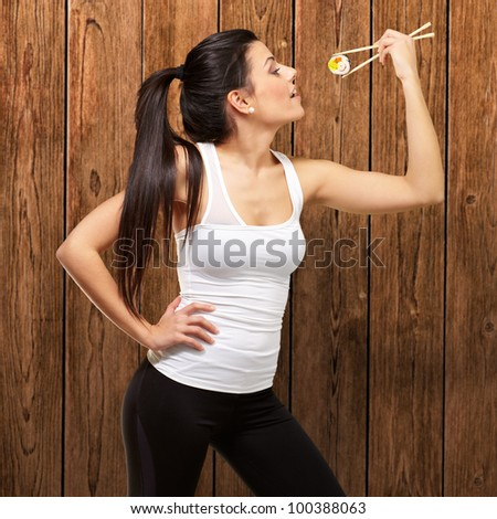 young pretty woman eating sushi against a wooden wall - stock photo
