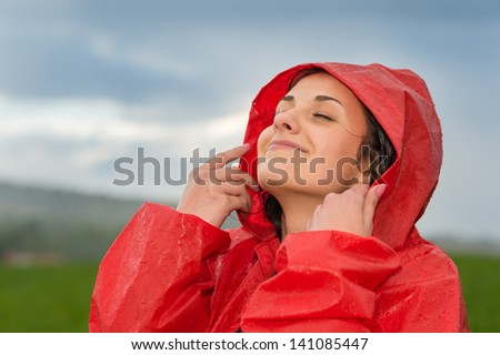 Young pretty woman enjoying raindrops on her face - stock photo
