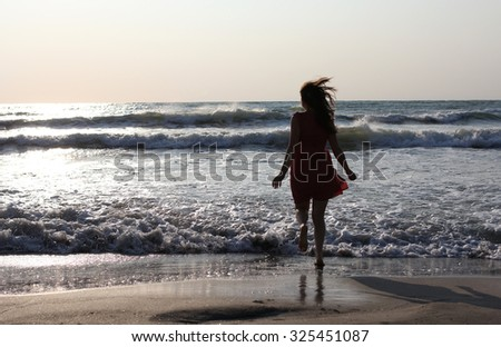 Young pretty woman enjoying the waves on the beach - stock photo