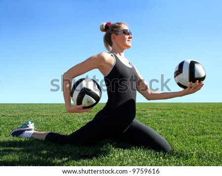 Young pretty woman exercising on green grass - stock photo
