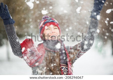 Young pretty woman having fun in the winter forest in motion - stock photo