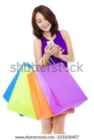 young pretty woman holding a cell phone to shop online over white background - stock photo