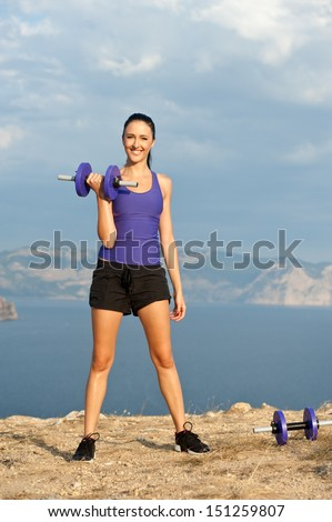 young pretty woman holding weights and doing fitness indoor - stock photo