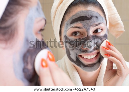 Young pretty woman in bathrobe and with towel on head applying facial mask in front of mirror in bathroom. Skin care and beauty concept - stock photo