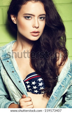 Young pretty woman in blue jucket posing against green wall in background. Lifestyle - stock photo