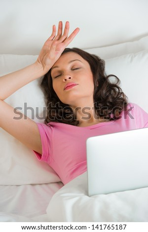Young pretty woman in dramatic pose with drama gesture laying on bed and holding tablet computer while chatting with her boyfriend, who offended her - stock photo