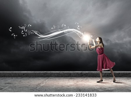 Young pretty woman in red dress playing flute - stock photo