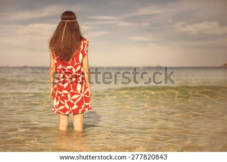 Young pretty woman in red dress standing and thinking on the sea  - stock photo